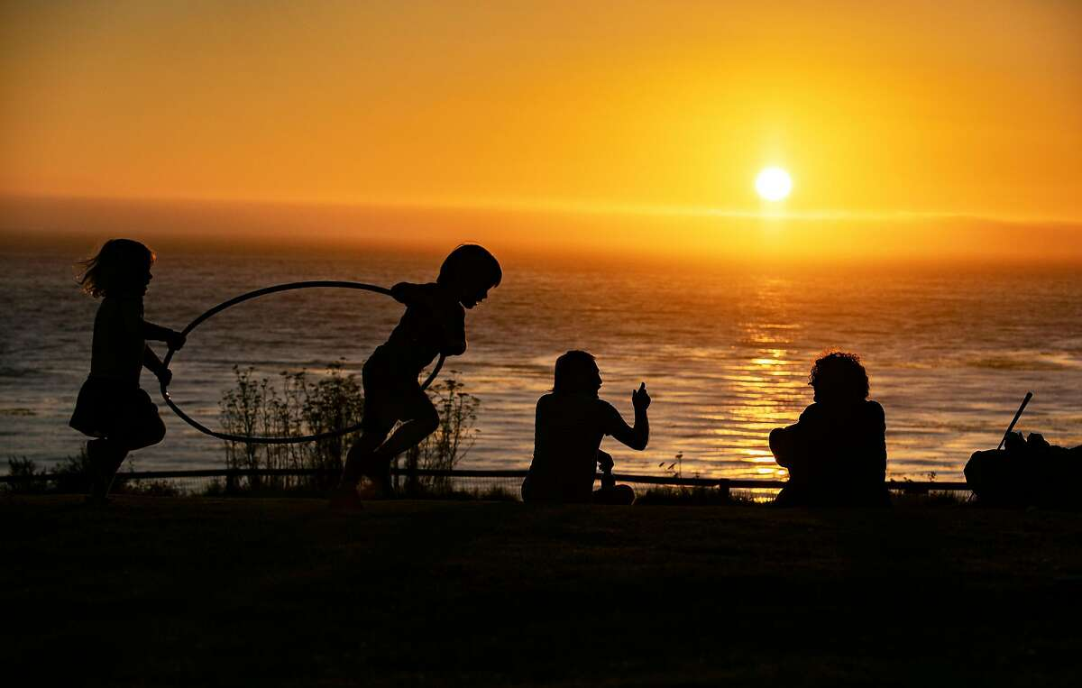 Guests relax on the lawn in front of the lodge as the sun sets at Esalen on Friday, August 30, 2019 in Big Sur, Calif.