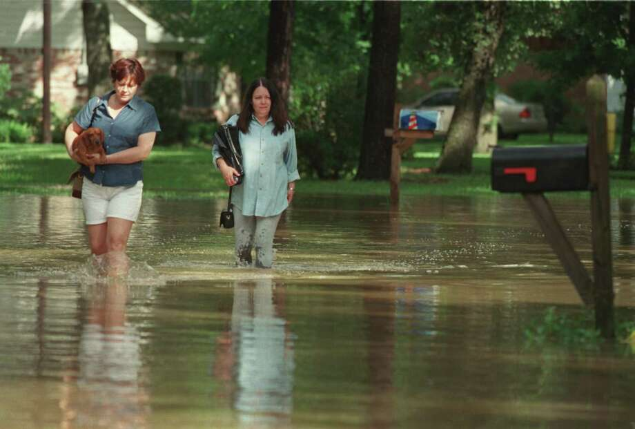 Residents wade down Imperial Street in November 2001 after flooding in the neighborhood, which is between Clear and Mary's creeks. Longtime Friendswood residents know that flooding problems related to Clear Creek have been a threat long before Hurricane Harvey caused widespread devastation in 2017. Proposition F in a bond package on the city's Nov. 5 ballot would provide $41 million for drainage work on the creek. Photo: Karl Stolleis, Staff / Houston Chronicle / Houston Chronicle