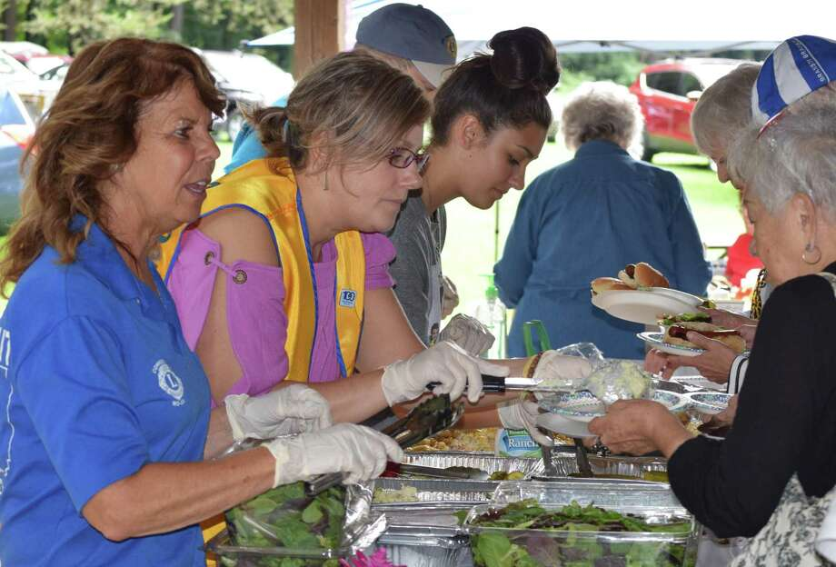 The New Milford Lions Club held its annual picnic for local seniors at Harrybrooke Park in town Aug. 23, 2019. The annual senior picnic, hosted by the New Milford Lions Club, featured a smorgasboard buffet of picnic fare. Above, from the left front back, Lions President Tammy Deak, left, Lion Ericka Onorato and volunteer Gabriella Vinci serve the guests. Photo: Deborah Rose / Hearst Connecticut Media / The News-Times  / Spectrum