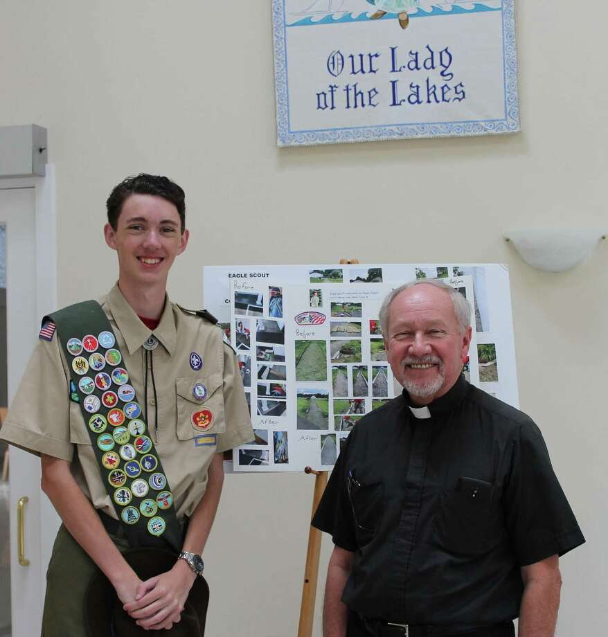 "Connor Woods is shown with the Rev. Gerald H. Dziedzic, pastor of Our Lady of the Lakes, standing in the vestibule of the church. Connor created the ""Thank you"" poster for the church as part of his Eagle Scout project. Photo: Courtesy Of The Woods Family / The News-Times Contributed"