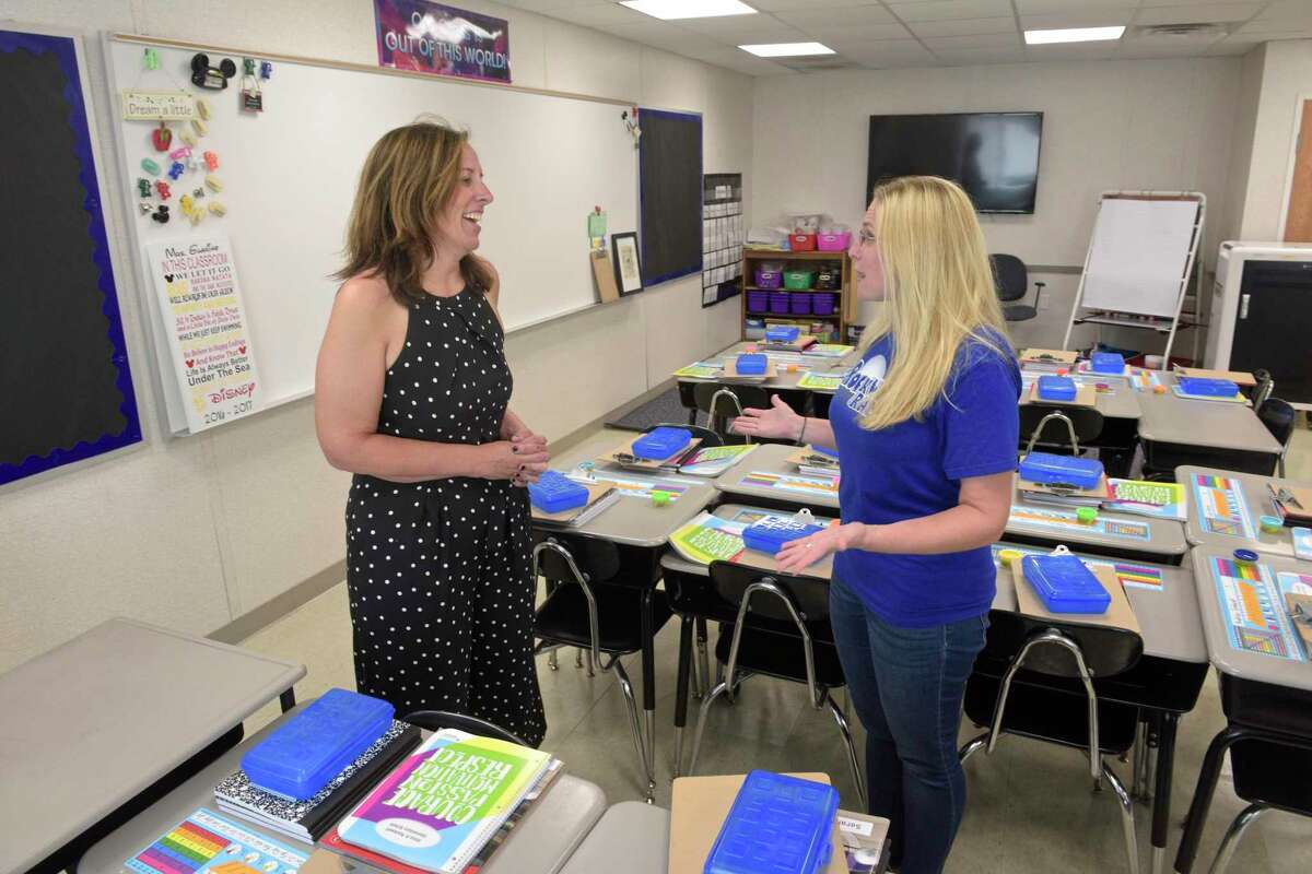 Superintendent Christine Carver talks with third-grade teacher Victoria Guarino in her portable classroom at Rockwell School in Bethel.