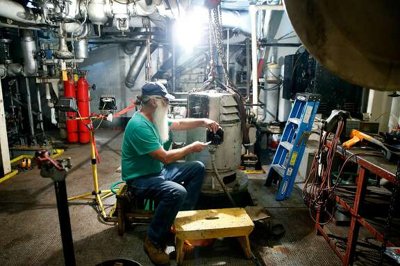 Rich Chivers, a volunteer electrician aboard the historic Red Oak Victory World War II ship, reestablishes an electrical connecton in the engine room in Richmond, Calif. on Tuesday, July 9, 2019.