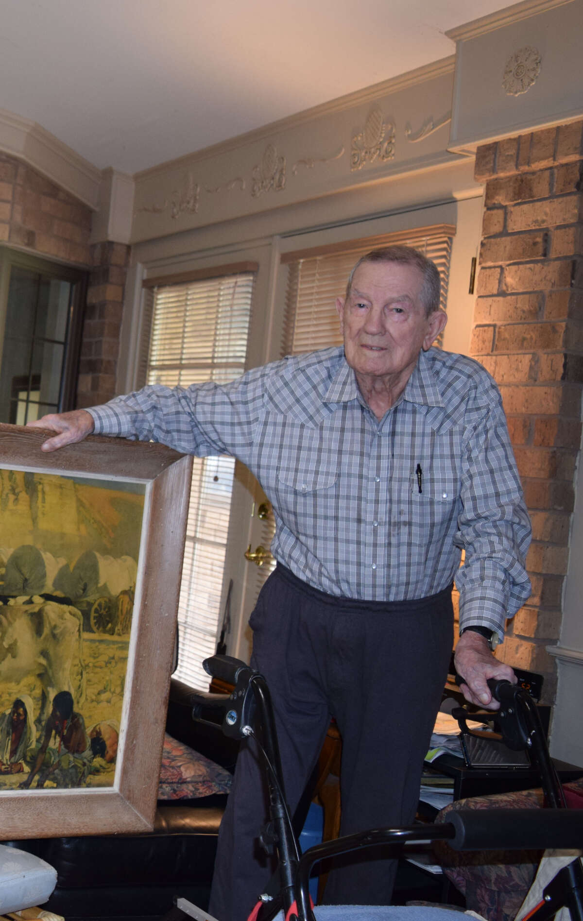 Harley Redin stands by a painting donated to the Conrad Lofts. (April 2019)