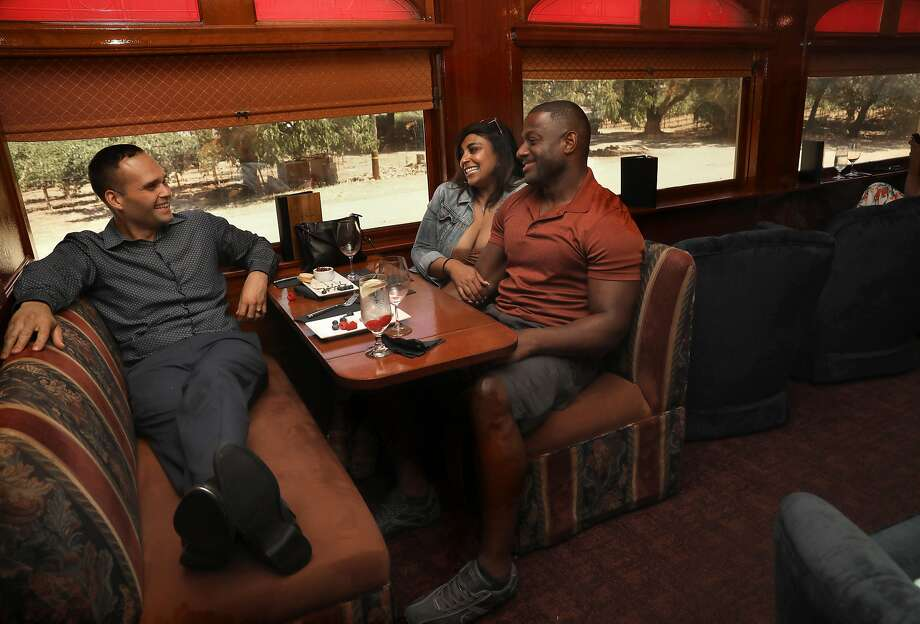 Food and beverage manager Stewart Mulky, left, gets to know passengers Clarissa Woods of Monterey and Demetric Antonio of San Diego while they have appetizers before lunch on the Napa Valley Wine Train. Photo: Liz Hafalia / The Chronicle