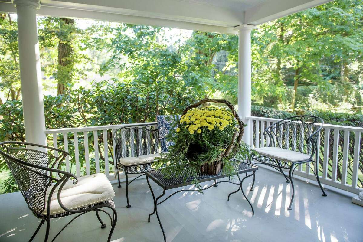 Creating zones for various purposes and adding natural elements, such as flowers, can transform a porch into an ideal entertaining space. Photo courtesy of Lisa O'Rourke/William Pitt Sotheby's International Realty New Canaan