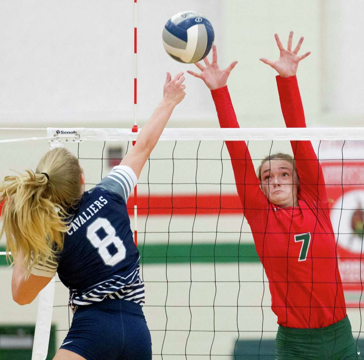 The Woodlands outside hitter Claire Arend (7) pressures a shot by College Park right side hitter Mallory Madison (8) during the first set of a District 15-6A high school volleyball match at The Woodlands High School, Tuesday, Sept. 3, 2019, in The Woodlands.