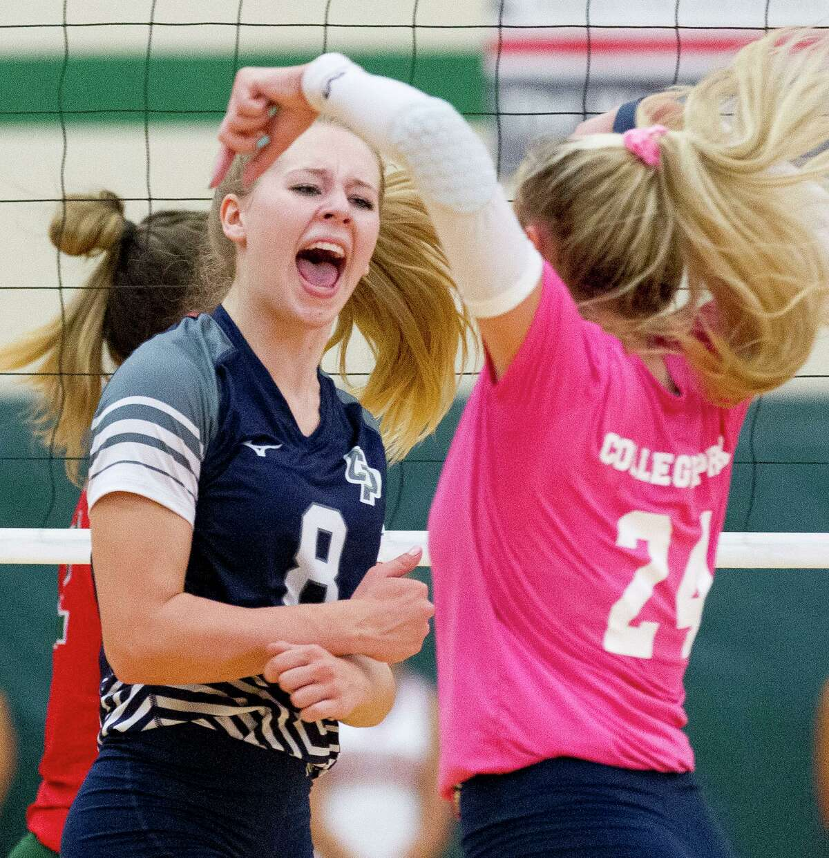 College Park right side hitter Mallory Madison (8) reacts in front of libero Caley Caffey (24) after scoring a point during the first set of a District 15-6A high school volleyball match at The Woodlands High School, Tuesday, Sept. 3, 2019, in The Woodlands.