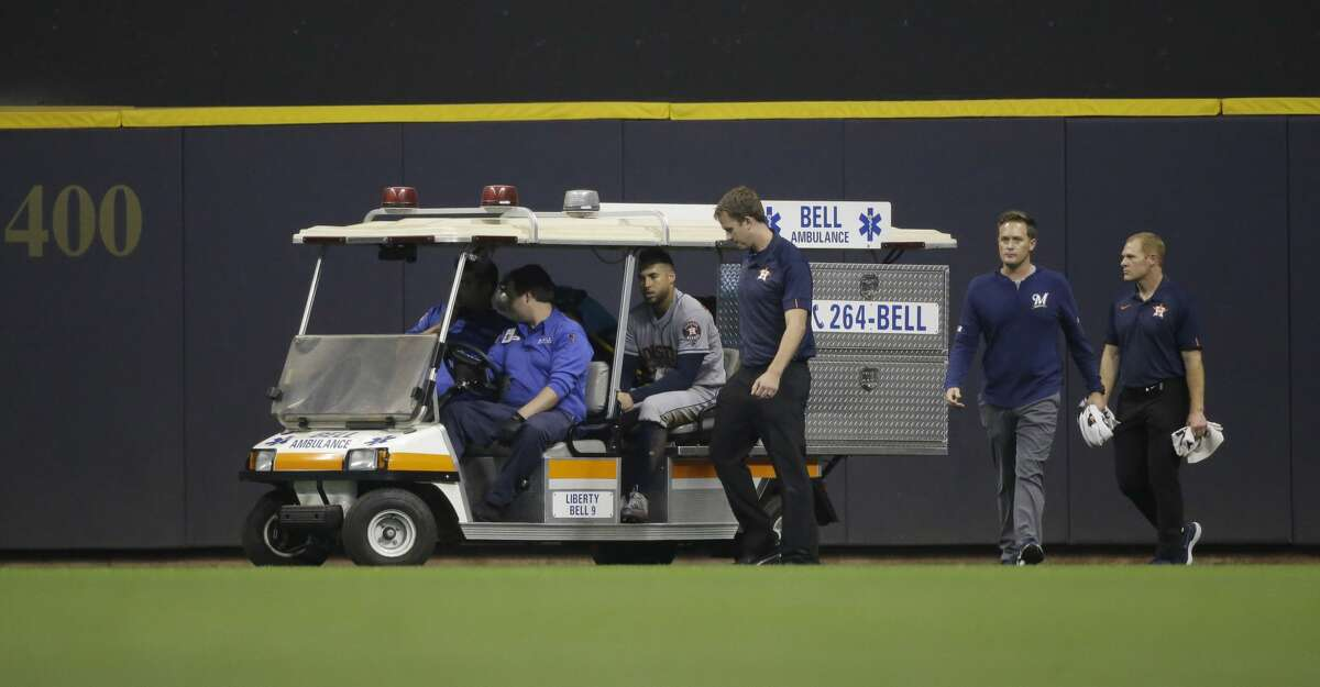Houston Astros' George Springer is taken off on a cart after being injured making a leaping catch on a ball hit by Milwaukee Brewers' Ryan Braun during the fifth inning of a baseball game Tuesday, Sept. 3, 2019, in Milwaukee. (AP Photo/Jeffrey Phelps)