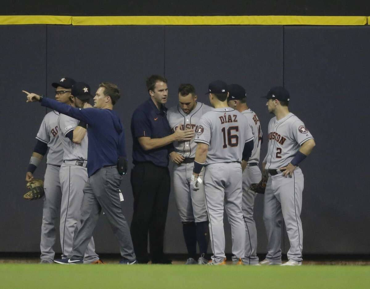 Houston Astros' George Springer, fourth from right, is helped up after he was injured making a leaping catch on a ball hit by Milwaukee Brewers' Ryan Braun during the fifth inning of a baseball game Tuesday, Sept. 3, 2019, in Milwaukee. (AP Photo/Jeffrey Phelps)