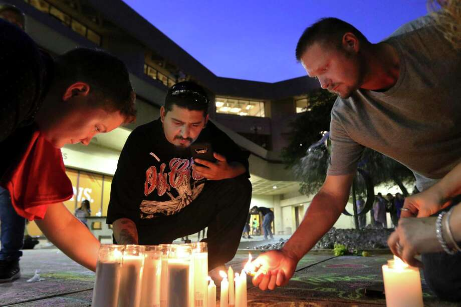 In this Sunday, Sept. 1, 2019, photo Crystal Harris, George Guerrero, and Curtis Patterson light candles in the shape of a cross on the ground of UTPB's quad in Odessa, Texas, to remember those who were killed in a shooting Saturday. (Ben Powell/Odessa American via AP) Photo: Ben Powell, MBI / Associated Press / (C) The Odessa American