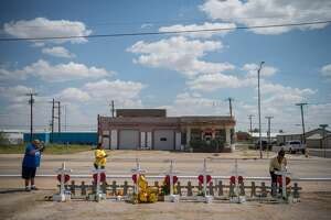 People pay their respects at a makeshift memorial created in memory of the victims killed in a recent mass shooting in Odessa, Texas, Sept. 3, 2019. Attacked across two cities, the victims were linked by fate and an enraged gunman. They were white and Hispanic, mothers and police officers, letter carriers and retirees. (Loren Elliott/The New York Times)