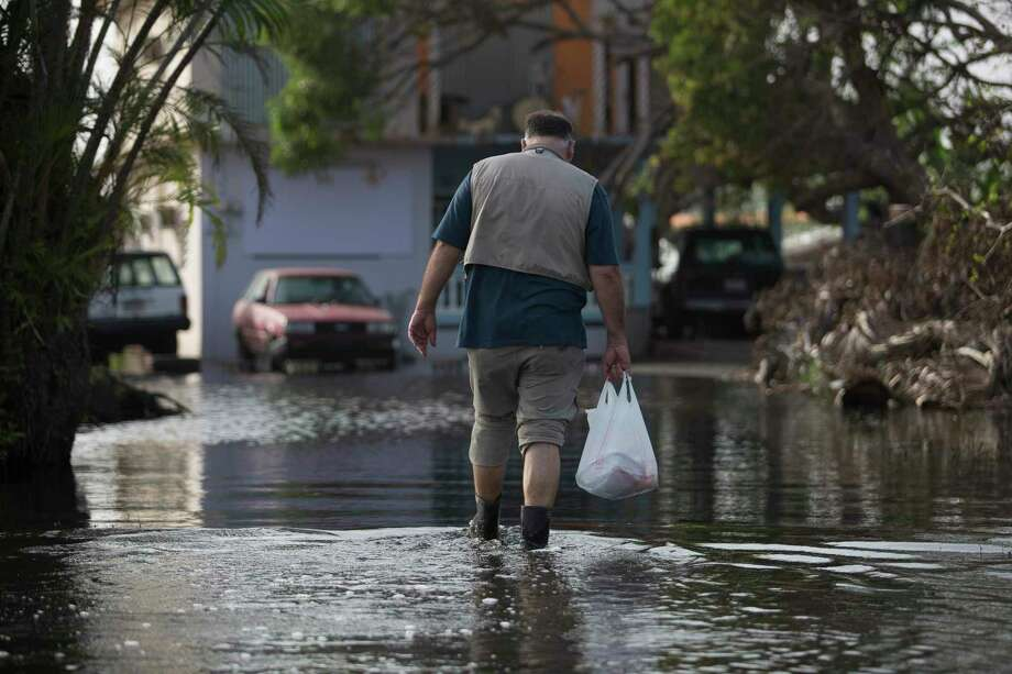 The chef José Andrés walks through water to deliver dinner to a 91-year-old veteran in Loíza, Puerto Rico, Oct. 19, 2017. Andrés' effort, by all accounts the largest emergency feeding program ever set up by a group of chefs, has started winding down. But it illustrates in dramatic fashion the rise of chefs as valuable players in a realm traditionally left to more established aid organizations. (Eric Rojas/The New York Times) Photo: ERIC ROJAS, STR / NYT / NYTNS