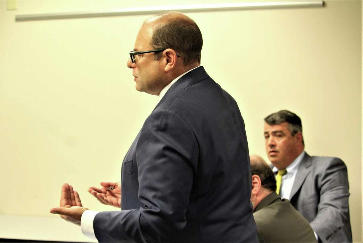 At a hearing at the state Department of Banking on Sept. 3, Ross Garber, shown standing, represented 1st Alliance Lending, an East Hartford company fighting a suspension by the department. At right is John DiIorio, the 1st Alliance CEO.