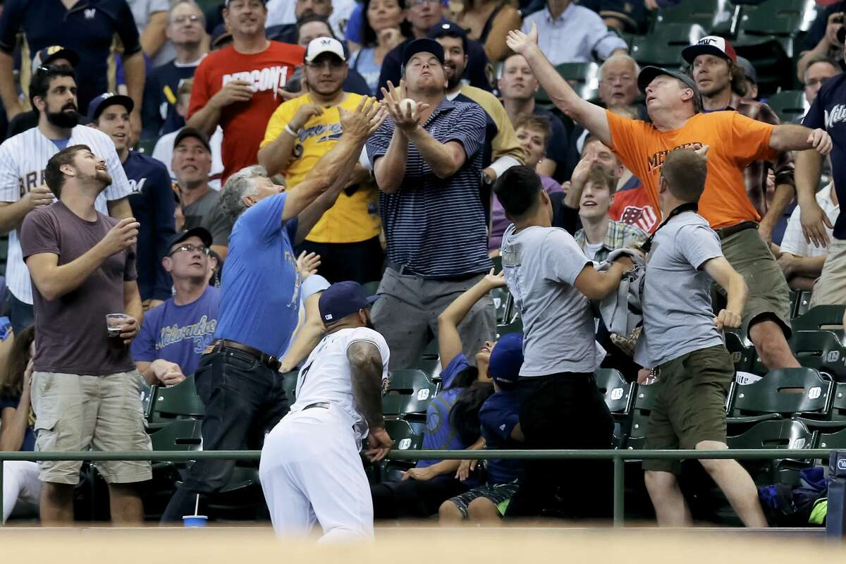 MILWAUKEE, WISCONSIN - SEPTEMBER 03: Fans attempts to catch a foul ball over Eric Thames #7 of the Milwaukee Brewers in the second inning against the Houston Astros at Miller Park on September 03, 2019 in Milwaukee, Wisconsin. (Photo by Dylan Buell/Getty Images)