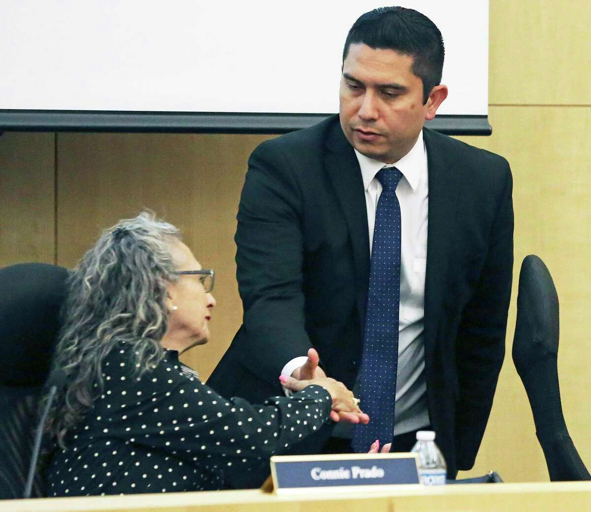 Former South San ISD superintendent Alex Flores shakes hands with Board President Connie Prado just before taking a buyout. South San has been plagued by governance issues, but consolidation isn't the solution. School finance reform is a better solution.