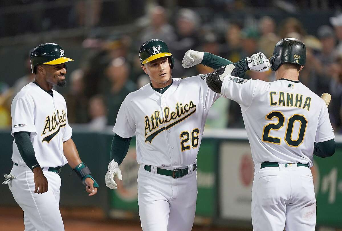 OAKLAND, CA - SEPTEMBER 03: Matt Chapman #26 of the Oakland Athletics is congratulated by Marcus Semien #10 and Mark Canha #20 after Chapman hit a three-run home run against the Los Angeles Angels of Anaheim in the bottom of the third inning at Ring Central Coliseum on September 3, 2019 in Oakland, California. (Photo by Thearon W. Henderson/Getty Images)