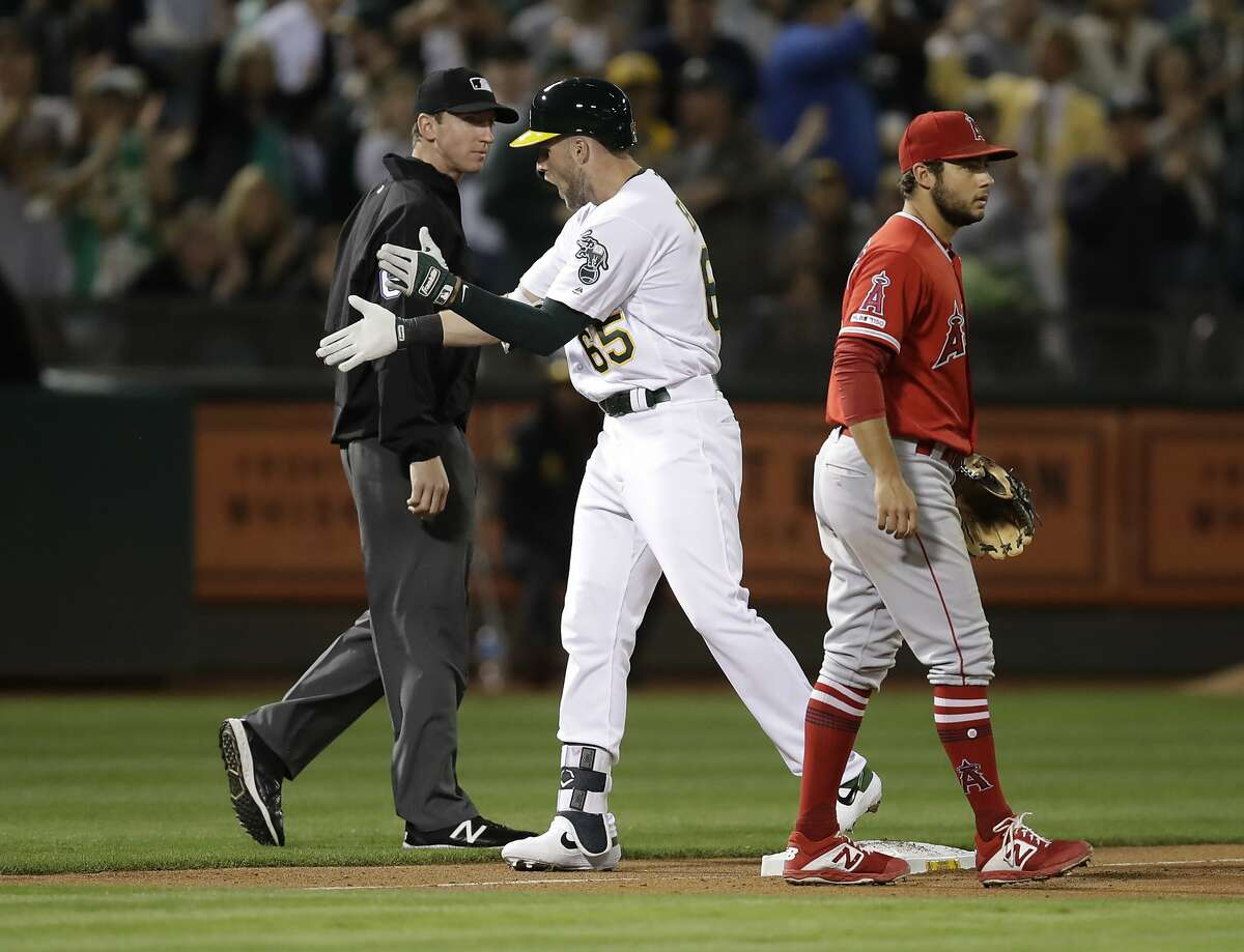 Oakland Athletics' Seth Brown (65) celebrates between Los Angeles Angels' David Fletcher, right, and third base umpire Alex Tosi after hitting an RBI triple during the second inning of a baseball game Tuesday, Sept. 3, 2019, in Oakland, Calif. (AP Photo/Ben Margot)