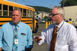 School Superintendent Dr. Chris Clouet, right, with school Finance Director Rick Belden outside the bus garage on Tuesday, Sept. 3, announced schools will open Wednesday, Sept. 4.