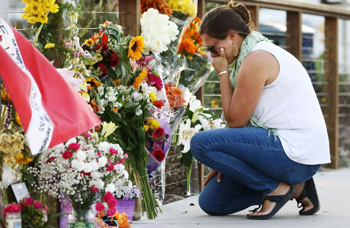 SANTA BARBARA, CALIFORNIA - SEPTEMBER 03: A woman looks emotional as she kneels at a makeshift memorial in Santa Barbara Harbor for victims of the Conception boat fire on September 3, 2019 in Santa Barbara, California. Authorities believe none of the 34 people below deck survived after the commercial scuba diving ship caught fire and sank, while anchored near Santa Cruz Island, in the early morning hours of September 2. Five crew members survived. (Photo by Mario Tama/Getty Images)