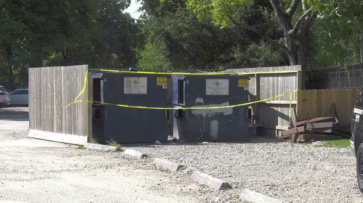 Houston police officers investigate the discovery of a body near dumpsters inside an apartment complex in the 5600 block of Antoine on Wednesday, Sept. 4, 2019, in Houston.