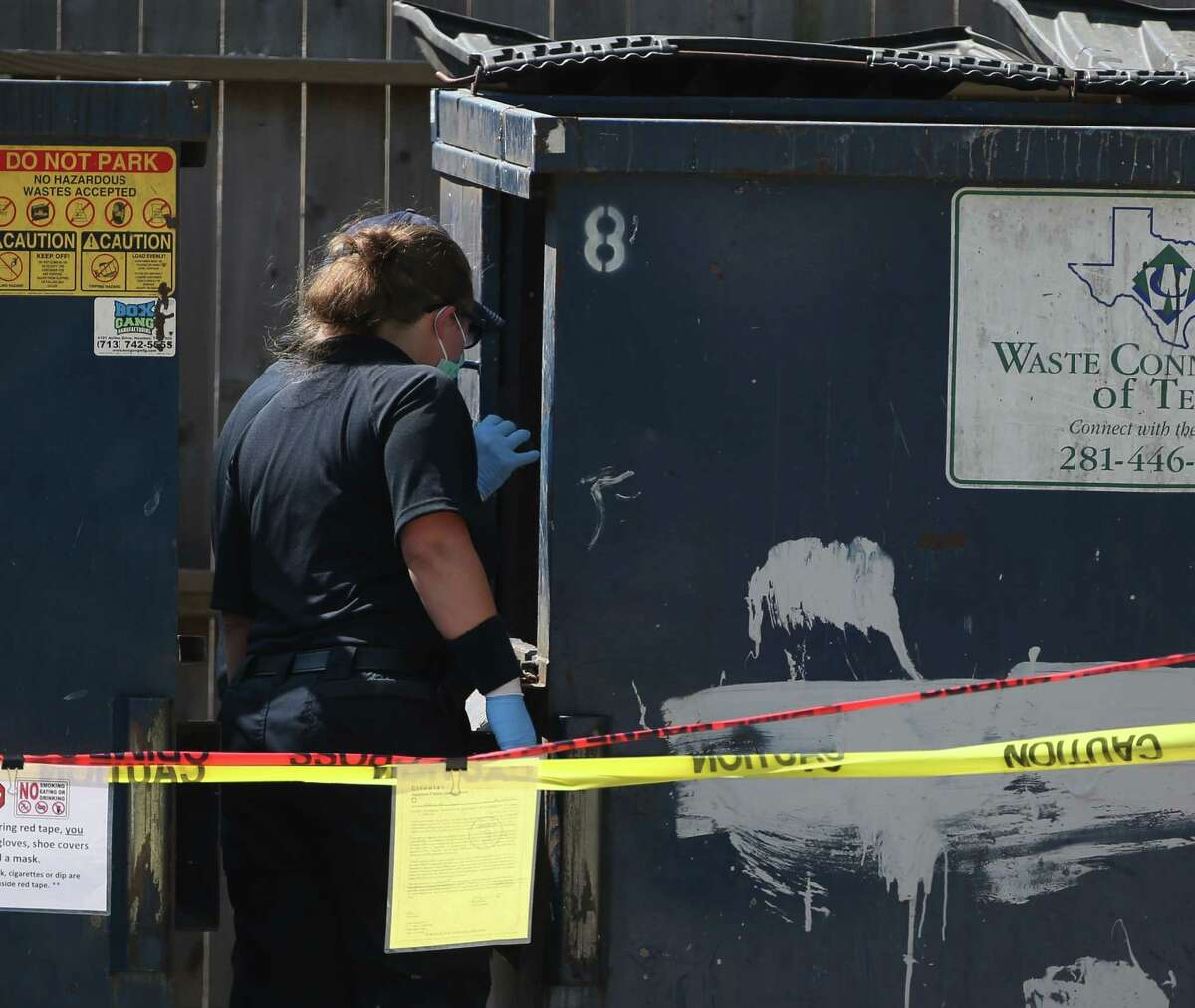 Houston Forensic Science Center investigators work at a scene where a deceased person was found in a dumpster at and apartment complex on the 5600 block of Antoine Drive on Wednesday, Sept. 4, in Houston.