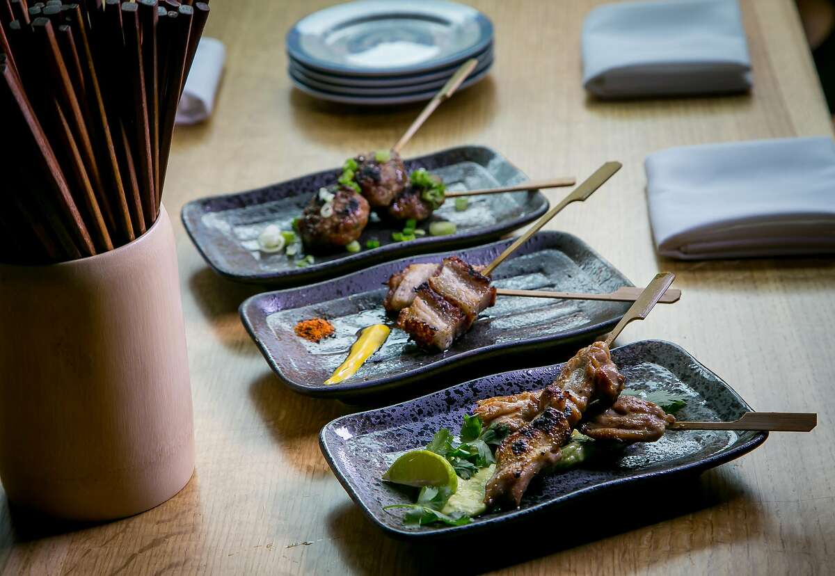 Skewers; front to back; Chicken Avocado, Pork Belly, and Japanese Meatball at Chubby Noodle in San Francisco, Calif., are seen on July 21st, 2015.