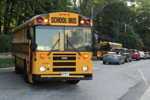 A school bus turns into Greenwich High as a long line of cars wait to leave on the first day of the 2017-2018 school year at Greenwich High School in Greenwich, Conn. Thursday, Aug. 31, 2017.