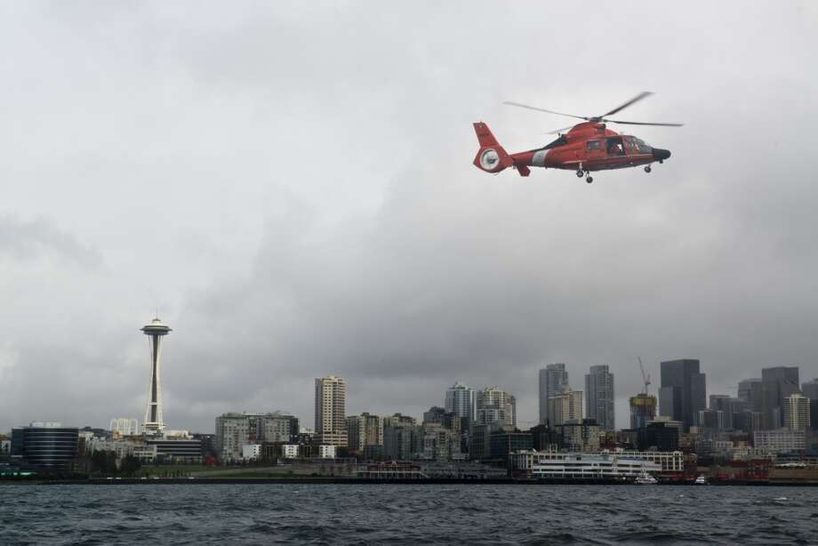 A Coast Guard Air Station Port Angeles MH-65 rescue helicopter flies over Elliott Bay. Photo: U.S. Coastguard