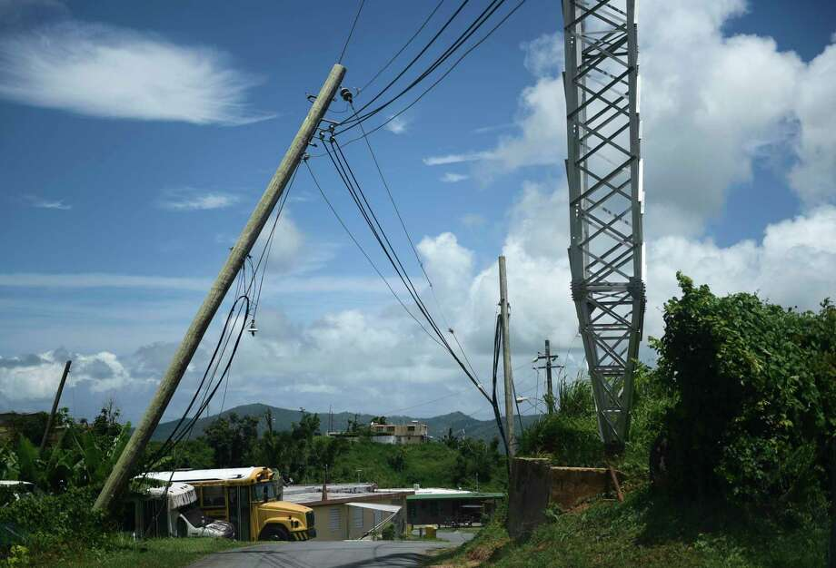 file - In this May 16, 2018 file photo, an electric power pole leans over the road in the Piedra Blanca area of Yabucoa, Puerto Rico, a town still mostly without power since it was struck by Hurricane Maria on Sept. 20. Puerto Rico's new governor announced on Sunday, Aug. 11, 2019 that she is suspending an upcoming $450,000 contract to rebuild and strengthen the island's power grid destroyed by Hurricane Maria. (AP Photo/Carlos Giusti, File) Photo: Carlos Giusti / Associated Press / Copyright 2018 The Associated Press. All rights reserved.