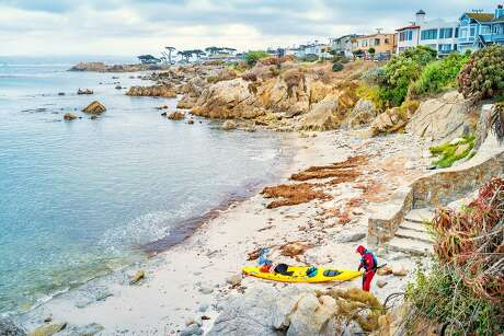 Person returns from a kayak trip at Pacific Grove with Lovers Point in the background in Monterey, California.