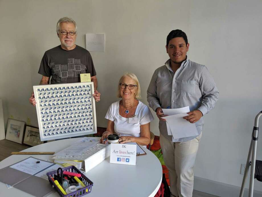 "RAC Exhibiting Member Gregg Welz, left, submitting his mixed media piece ""Ebb and Flow"" to RAC Board Exhibition Chairperson Eunice Roy and RAC Gallery Assistant Leo Gonzalez. Photo: Rowayton Arts Center / Contributed Photo"