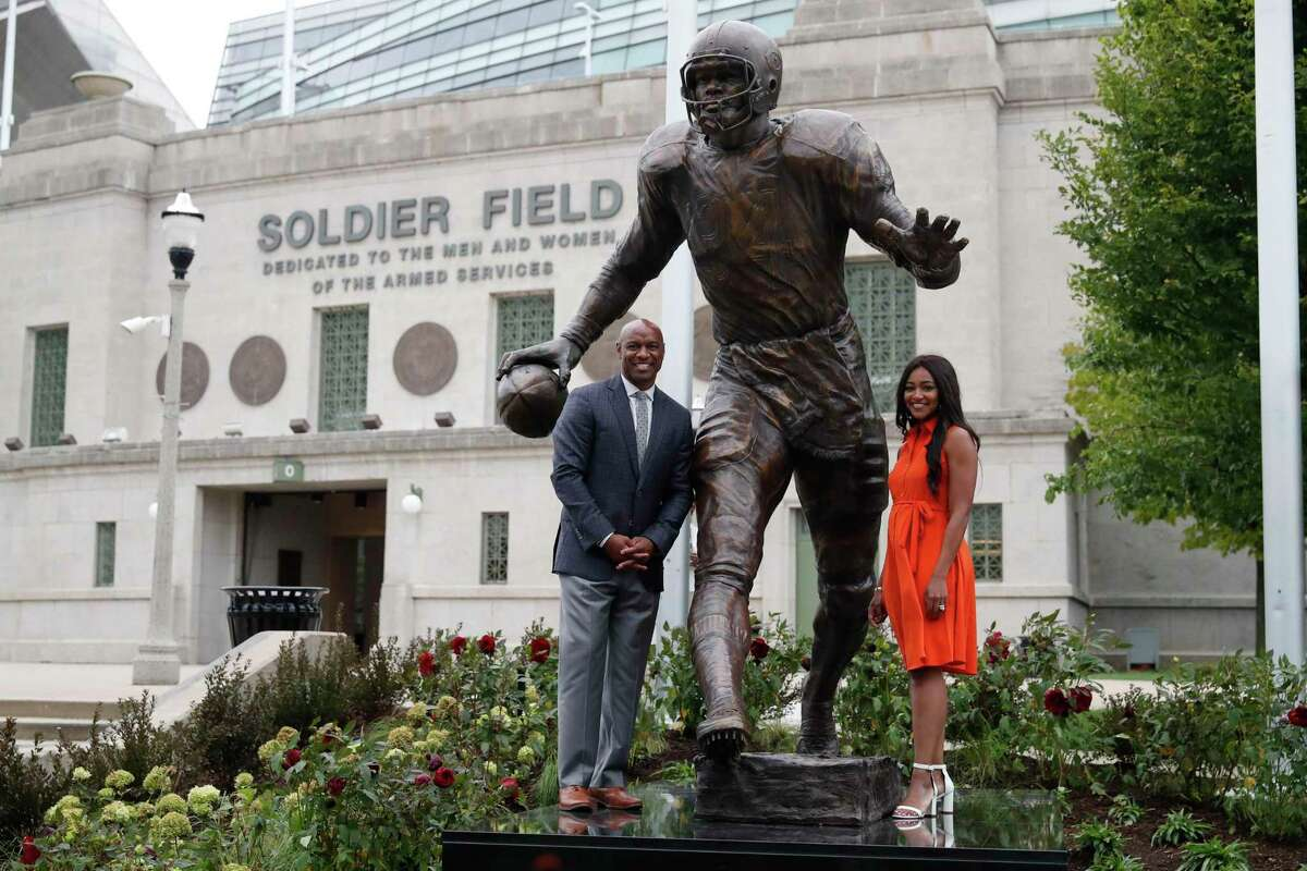 Jarrett Payton, son of former Chicago Bears and Pro Football Hall of Fame running back Walter Payton and his sister Brittney Payton, stand below the newly dedicated statue of Payton, outside Soldier Field after an unveiling ceremony of statues honoring George Halas and Payton, Tuesday, Sept. 3, 2019, in Chicago. The Bears and Packers will face off in the first game of the NFL's 2019 season on Thursday, Sept. 5, 2019 at Soldier Field.
