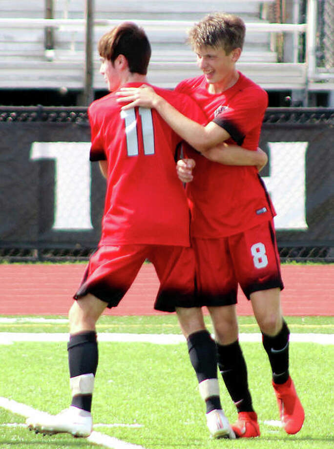 Alton's Brayden Decker (8) had a goal and two assists Tuesday in his team's 4-2 win over Belleville East. he is shown being congratulated by teammate Hayden Batchelor after a goal Saturday against Rochester in the Kahok/Redbird Tournament. Photo: Pete Hayes | The Telegraph
