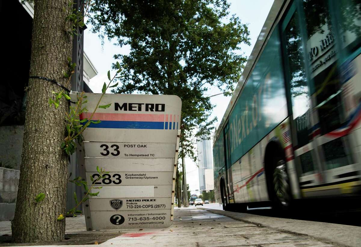 A Metropolitan Transit Authority sign sits on the ground along Post Oak Boulevard in Houston on July 17, 2019, as a bus passes by.