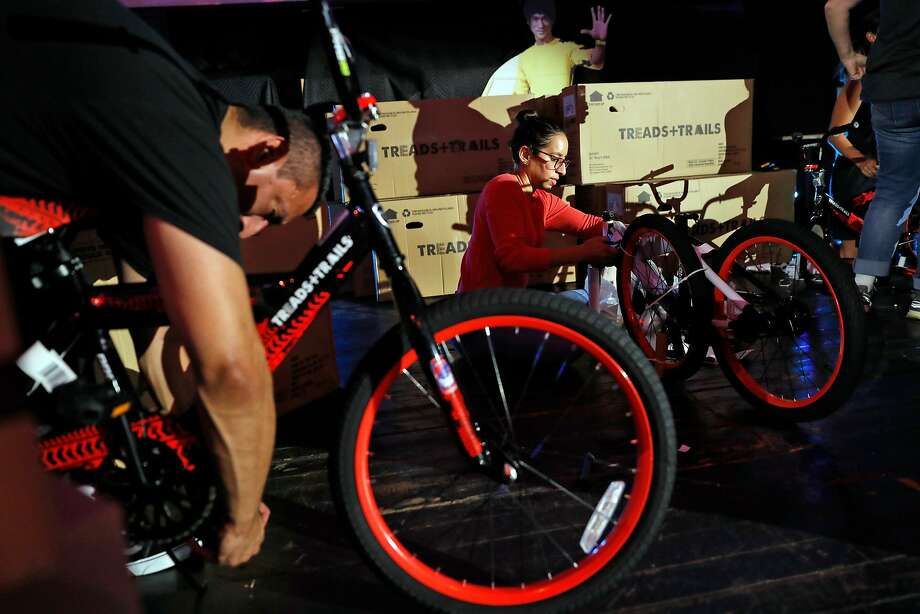 Max Cortez (left) and Colleen Pineda assemble free bikes for McCoppin Elementary School children. Photo: Photos By Scott Strazzante / The Chronicle
