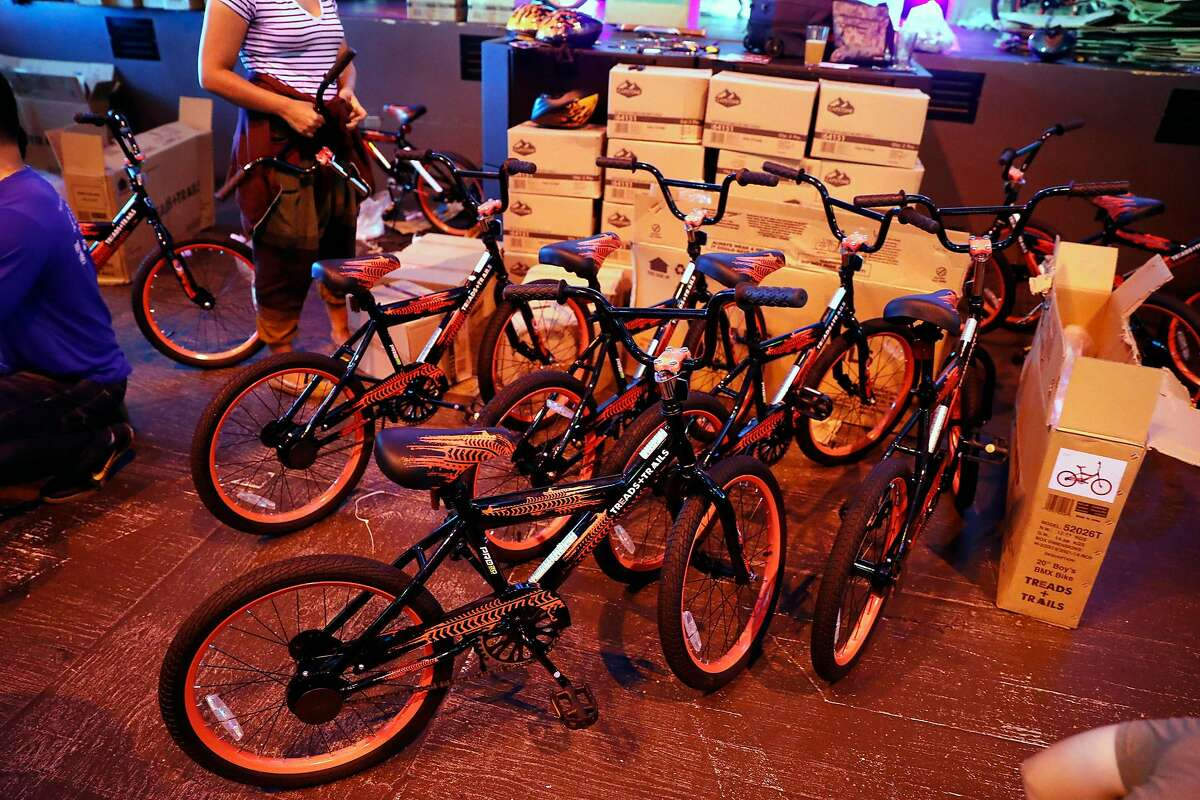 Volunteers help build bikes for students at McCoppin Elementary School at Emporium Arcade Bar in San Francisco, Calif., on Tuesday, September 3, 2019.