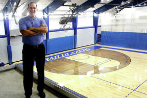 Lewis and Clark Community College athletic director Doug Stotler with the River Bend Arena's new hardwood basketball/volleyball court in the background. The court is one of many refurbishments at the arena which opened in 1993.