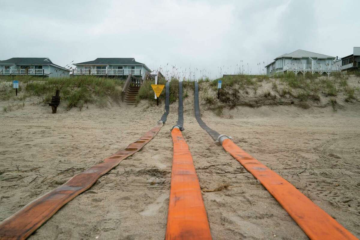 Hoses extend to the ocean in anticipation of flooding before the arrival of Hurricane Dorian on Wednesday in Carolina Beach, N.C. The state recently established an Office of Recovery and Resiliency in part to halt the cycle of destruction and rebuilding after storms.