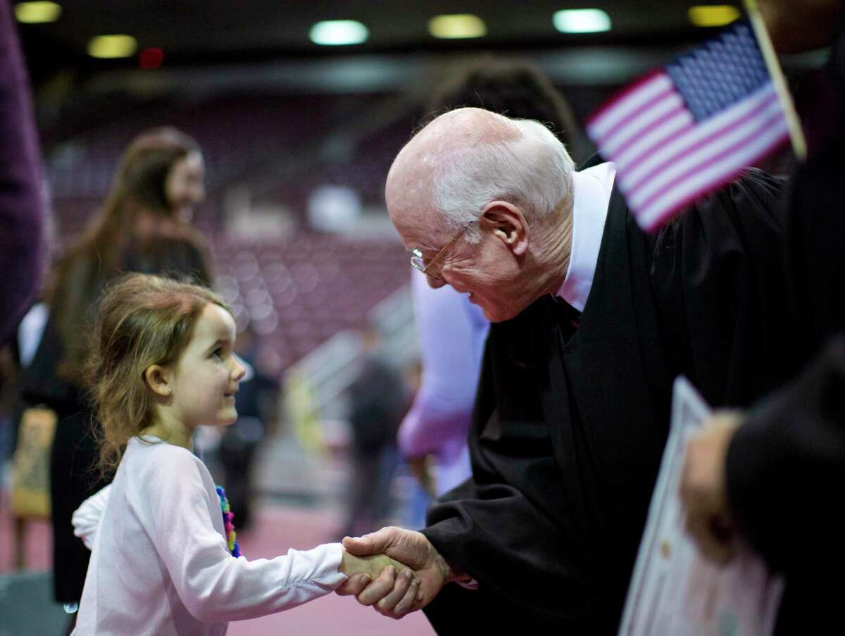 United States District Judge Lynn N. Hughes greets Haylee Brown, 6, the granddaughter of a newly naturalized citizen after the Oath of Renunciation and Allegiance, Thursday, Feb. 20, 2014, in Houston. ( Marie D. De Jesús / Houston Chronicle )