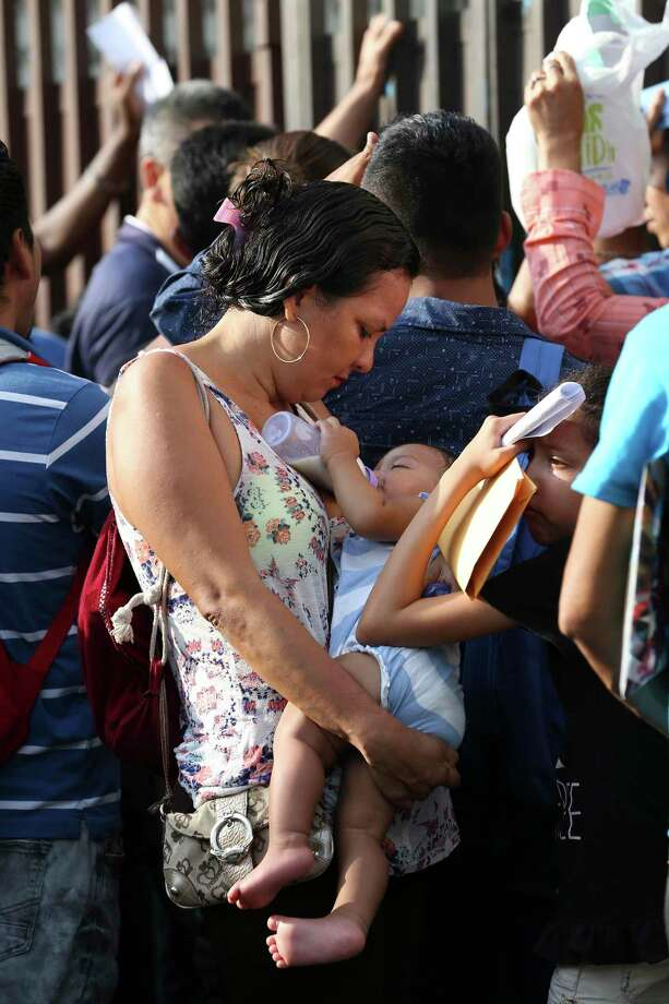 La hondureña Medli Solís protege a su hija, Yarizne Monserrat, de las condiciones climáticas en Tapachula, México, el lunes 7 de septiembre de 2019. Photo: Jerry Lara /San Antonio Express-News / © 2019 San Antonio Express-News
