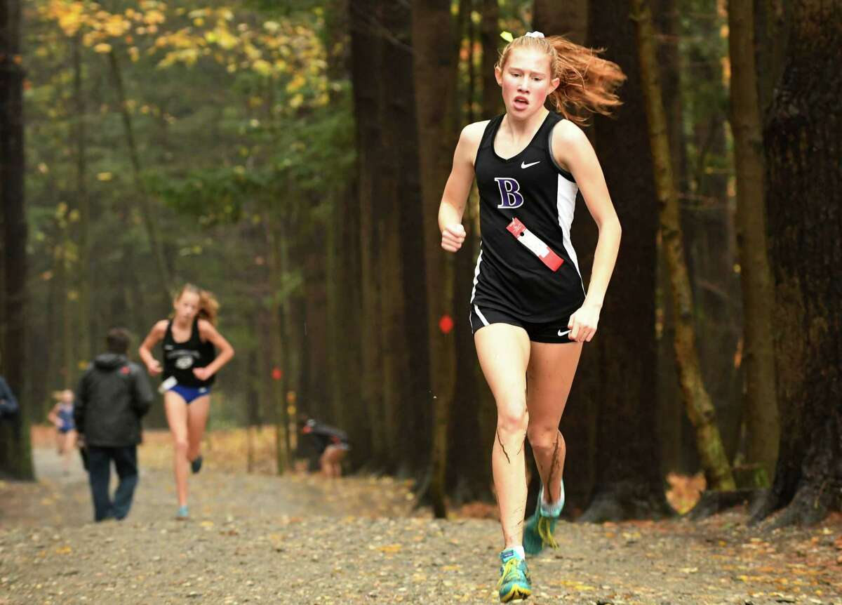 Faith DeMars of Ballston Spa leads Ella Kurto of Saratoga Springs, left, out of the woods to take second place in the Class A Section II Cross Country Championships race at Saratoga Spa State Park on Friday, Nov. 2, 2018, in Saratoga Springs, N.Y. (Will Waldron/Times Union)