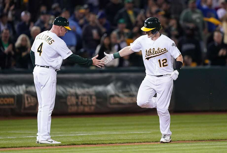 Sean Murphy #12 of the Oakland Athletics is congratulated by third base coach Matt Williams #4 after Murphy hit a solo home run against the Los Angeles Angels of Anaheim in the bottom of the fifth inning at Ring Central Coliseum on September 04, 2019 in Oakland, California. The home run was Murphy's first career hit. Photo: Thearon W. Henderson, Getty Images
