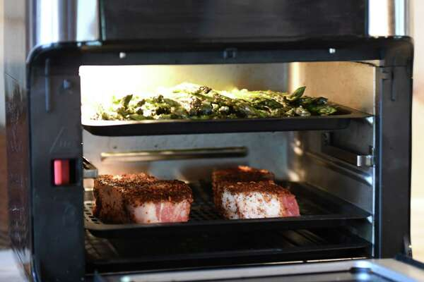 Pork chops and asparagus are cooked in an air fryer oven by Marissa Mancuso on Friday, Aug. 23, 2019, in Rotterdam, N.Y. (Will Waldron/Times Union)