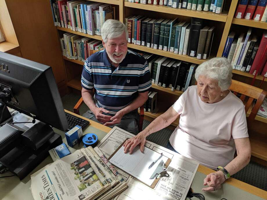 "Obituary project volunteers John Driscoll and Marlene ""Pete"" Eldridge, logging information into the computer. Photo: Contributed Photo / Connecticut Post"