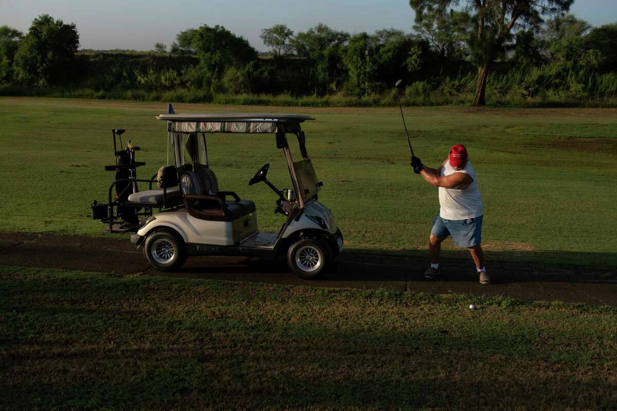 """Greg Heiy wears a """"Make America Great Again"""" hat as he golfs on the course at River Bend Resort and Golf Club, which hugs the Rio Grande in Brownsville, Texas, Aug. 30, 2019. The community could find itself physically divided by President Donald Trump's proposed border wall with Mexico. (Callaghan O'Hare/The New York Times)"""