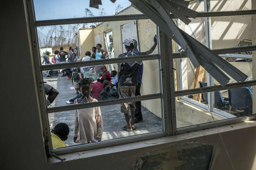 A group of people originally from Haiti wait in the hope of getting a seat on an evacuation plane at the Treasure Cay International Airport in the Bahamas on Tuesday, Sept. 4, 2019. Days after Hurricane Dorian bore down on the Bahamas as one of the strongest Atlantic storms on record, harrowing stories of survival have trickled out. (Daniele Volpe/The New York Times)