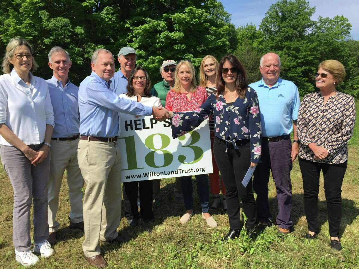 The Wilton Woman's Club presents a check last June for $28,000 to the Wilton Land Conservation Trust and its project Save 183 Ridgefield Road. From left are Donna Merrill, Scott Bogan, Craig Johnson, Mark Rice, Kathy Poirier, Bruce Beebee, Liz Salguero, Dianne deWitt, Andrea Bates, Mike Foster, and Jennifer Toll.