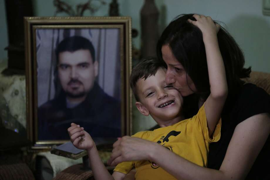 Suzan Suleiman kisses her son Youssef, 6, at her home in Homs. Her husband, Iyad Suleiman, vanished after being kidnapped in 2013 by militants from the al Qaeda-linked Al Nusra Front. Photo: Hassan Ammar / Associated Press