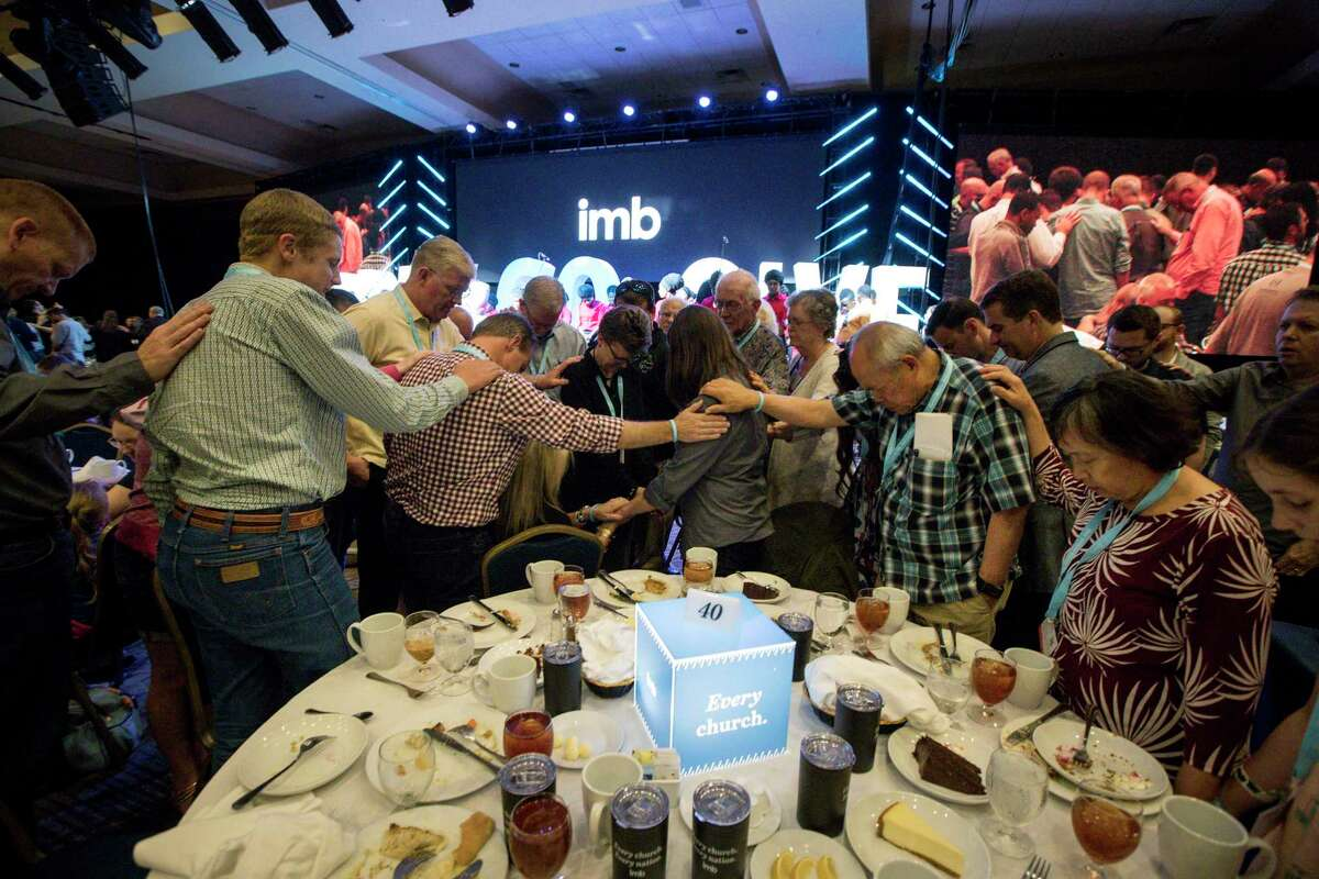 People pray for new missionaries during an International Mission Board dinner on the eve of the the Southern Baptist Convention's annual meeting on Monday, June 10, 2019, in Birmingham. The missionary program receives the lion's share of funds - nearly $100 million in 2018 - in the SBC's annual budget.