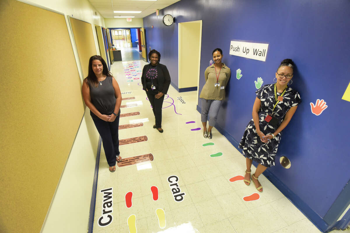 Tina Cascone, left, assistant principal at Sheridan Preparatory Academy: A Community School, Abigail Gomes, second from left, the school's community school site coordinator, Alyssa Joseph, third from left, St. Peter's program coordinator for the Creating Healthy Schools and Communities, and Zuleika Sanchez-Gayle, principal at Sheridan Preparatory Academy, stand in the sensory path hallway of the school on Thursday, Sept. 5, 2019, in Albany, N.Y. (Paul Buckowski/Times Union)